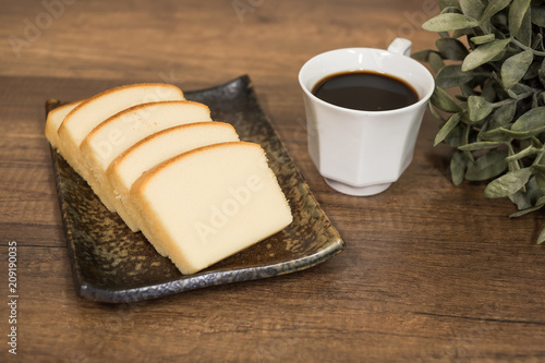Wall mural Homemade plain butter cake soft and moist. Slice of butter cake on plate and serve with black coffee on wooden background