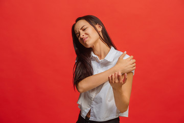 Young woman overwhelmed with a pain in the shoulder
