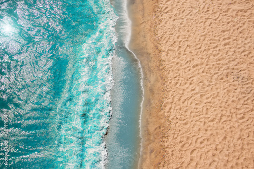 Leinwanddruck Bild Coastline Beach Ocean waves with foam on the sand. Top view from drone.