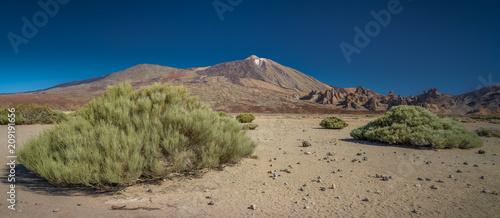 Aluminium Nachtblauw Vulkangipfel in umgebender Felslandschaft mit grünen Büschen im Vordergrund