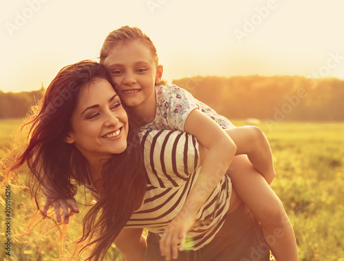 Leinwanddruck Bild Happy enjoying loving mother hugging her playful laughing kid girl on sunset bright summer background. Closeup toned color bright portrait.