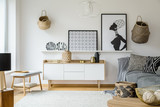Posters and plates above wooden cupboard in boho living room interior with grey sofa. Real photo - 209197823