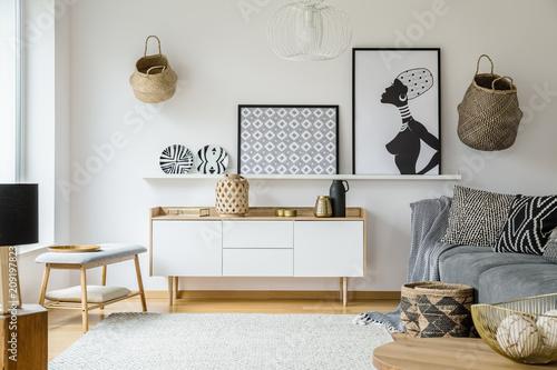 Plakaty i talerze nad drewnianą szafką w salonie boho z szarej kanapie. Prawdziwe zdjęcie