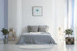 Grey bed between plants in white simple bedroom interior with poster and round rug. Real photo