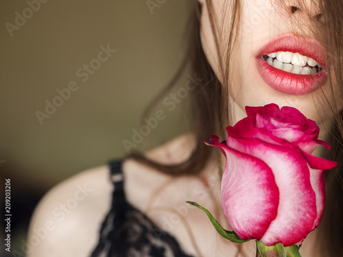 Close-up shot of sexy woman lips with red lipstick and beautiful red rose.