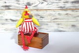 Soft handmade rooster cock toy in red shorts and red stripes in white dot paws sits on wooden box - 209207419