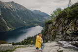 Young beautiful couple in yellow raincoats standing on a rock against a backdrop of a mountain lake in the Tatra National Park in Poland