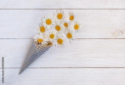 dzikie białe stokrotki i rożek waflowy na białym tle drewnianych