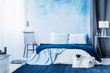 Navy blue carpet in minimal bedroom interior with blanket on bed next to a chair and under a lamp - 209212223