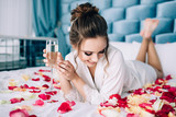 Morning of the bride. The bride lies on rose petals and drinks champagne - 209214479