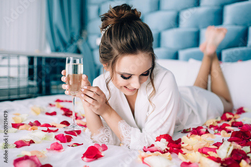 Morning of the bride. The bride lies on rose petals and drinks champagne