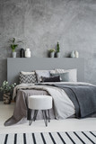Striped carpet and stool in grey bedroom interior with sheets on bed with headboard. Real photo - 209214645