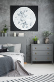 Moon poster above grey cabinet and bed in modern bedroom interior with plants. Real photo