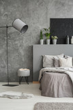 Lamp and stool next to bed with pillows and bedhead in grey bedroom interior with poster. Real photo - 209214687