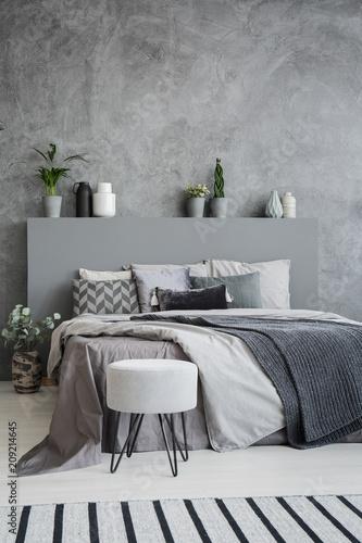 Dywan w paski i taboret w szarym wnętrzu sypialni z pościelą na łóżku z zagłówkiem. Prawdziwe zdjęcie
