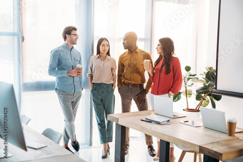 Poster group of multicultural business people having conversation during coffee break in office