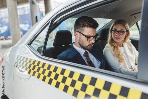 young couple in formal wear and eyeglasses sitting together in taxi
