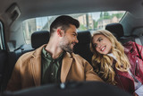 Fototapety beautiful happy young couple smiling each other while sitting together in car