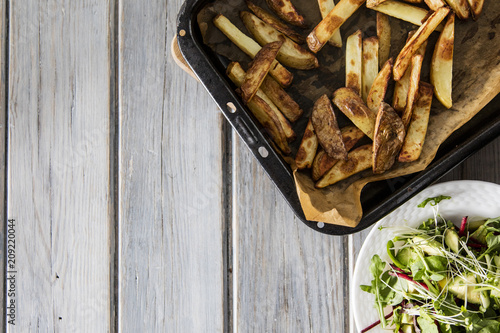 Homemade baked skin on potato fries on a rustic wooden background - 209220044