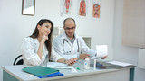 Dreamy female doctor asking her colleague what to answer to a phone message - 209223282