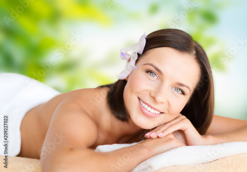 wellness and beauty concept - close up of beautiful woman at spa over green natural background © Syda Productions