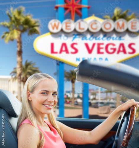 travel, road trip and people concept - happy young woman driving convertible car over welcome to fabulous las vegas sign background