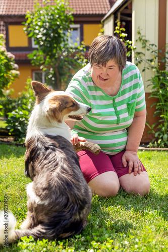 Frau mit geistiger Behinderung und ein Hund im Garten, Hilfe durch Therapiehund