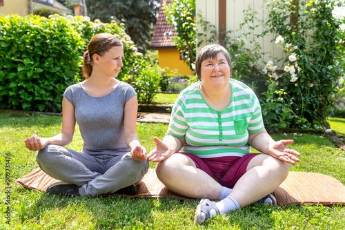 Yogalehrerin und geistig behinderte Frau sitzen im Garten, Entspannungsübungen und Sonderpädagogik