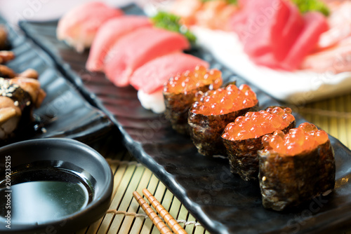 Fotobehang Sushi bar Sushi with chopsticks and soy sauce. Sushi roll japanese food in restaurant. Salmon roe Sushi set with salmon, vegetables, flying fish roe and caviar closeup. Japan restaurant menu