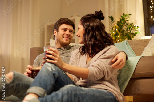 Wall mural hygge, leisure and people concept - happy couple drinking coffee and eating at home