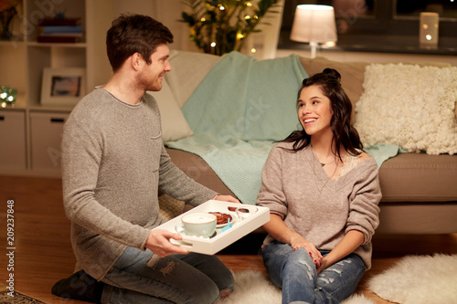 Sticker leisure, hygge and people concept - happy couple with food on tray at home