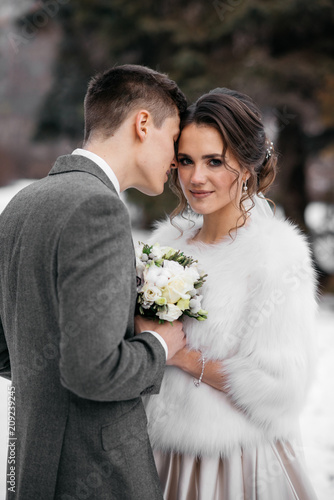 Foto Murales The bride and groom stand in the winter park. Vertical portrait