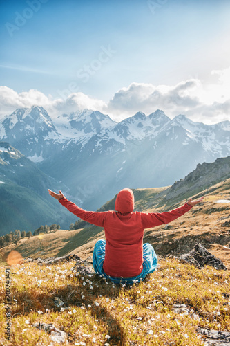 Woman doing yoga exercise on the top of mountain