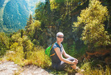 Woman hiker sitting on the top of mountain