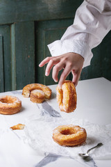 Boy's hand hold homemade puff pastry deep fried donuts or cronuts with sugar standing on crumpled paper over white marble kitchen table.