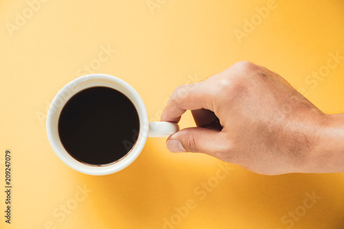 Wall mural Hand of a man holding a hot black coffee cup on yellow background
