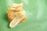 Crispy fried golden sliced banana on green net mat - 209251896