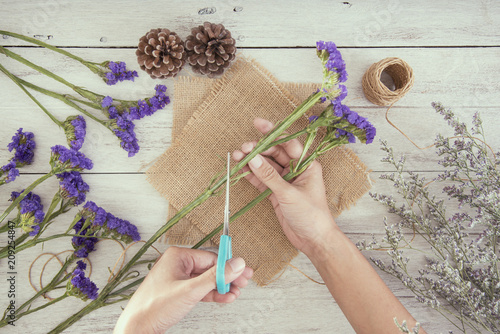 Foto Murales Top view hand of woman florist creating bouquet of flower on table shop.