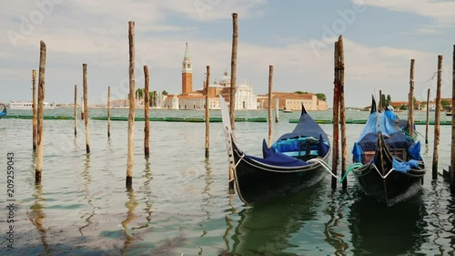 The symbol of Venice is the traditional gondola boat. Rock on the waves, moored near the shore