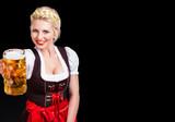 attraktive junge Frau im Dirndl mit Bierkrug vor schwarzem Hintergrund