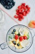 flat-lay of a blender and fresh seasonal berries and fruits over white background, cooking preparing smoothie, detox, healthy clean eating