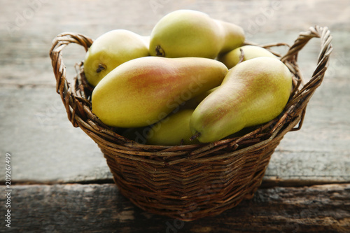 Foto Murales Ripe and sweet pears in basket on grey wooden table