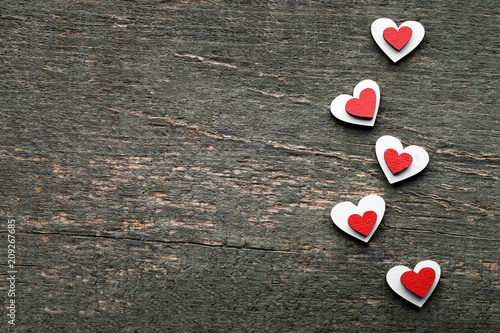 Red and white wooden hearts on grey table