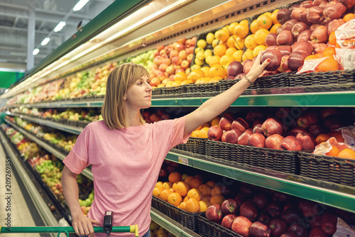 Slender woman standing in front of a row of fruits in a grocery store. She is picking up an apple.
