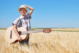 child boy with guitar is in the yellow wheat field, bright sun, summer landscape - 209270460