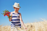 child girl walking in the yellow wheat field, bright sun, summer landscape - 209270483