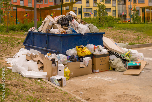 Crowded dumpster in the area of construction of a new urban residential area