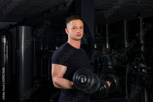Poster young male athlete bodybuilding in blue sportswear doing exercises with dumbbells in a dark gym