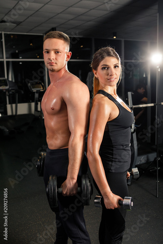 Plexiglas Fitness young beautiful couple of athletes doing exercises in a dark gym