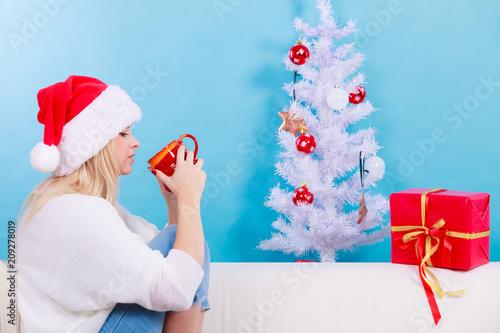 Woman in santa christmas hat drinking tea or coffee
